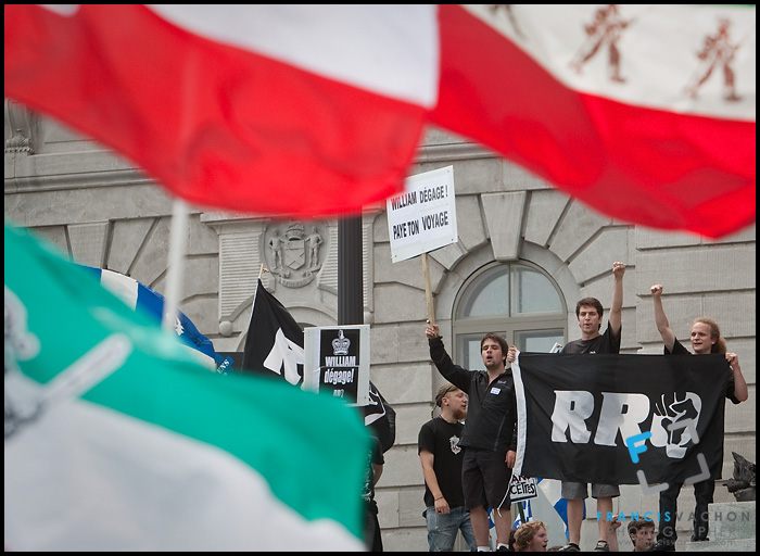 Protesters wave flag and sign at the door of the Quebec National Assembly as they demonstrate against the the royal visit  by Britain's Duke and Duchess of Cambridge, Prince William and Kate Middleton, during a demonstration organized by the pro-independence group Réseau de Résistance du Québecois  in Quebec City Sunday July 3, 2011.
