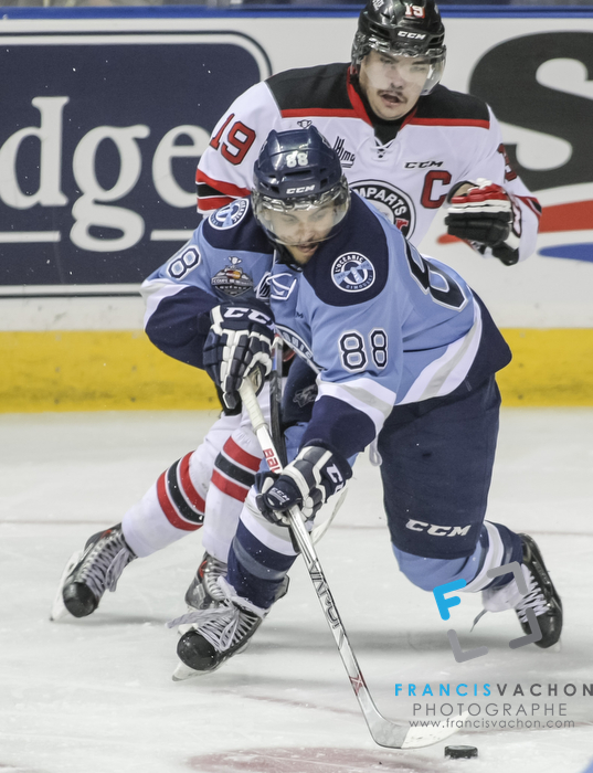 Quebec Remparts forward Kurt Etchegary and Rimouski Oceanic forward  Michael Joly fight for the puck in third period action at the Memorial cup tiebreaker at Le Colisee Pepsi in Quebec city Thursday May 28, 2015.