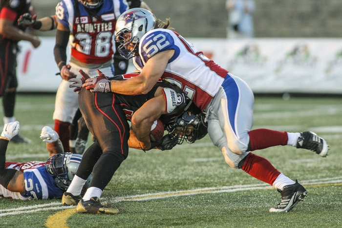Montreal Alouettes' Mitchell White tacles  Ottawa Redblacks' Ernest Jacson during CFL action in Quebec City on Saturday June 13, 2015. Francis Vachon/Postmedia Network
