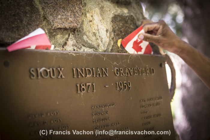 A woman adjust a Canadian Flag on a commemorative plaque at an Sioux Indian graveyard near Portage La Prairie, Manitoba, Monday August 17, 2015.