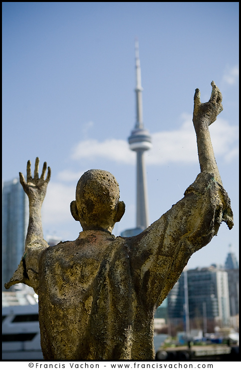 CN Tower is seen behind monument of the Irish Famine Memorial in Toronto.